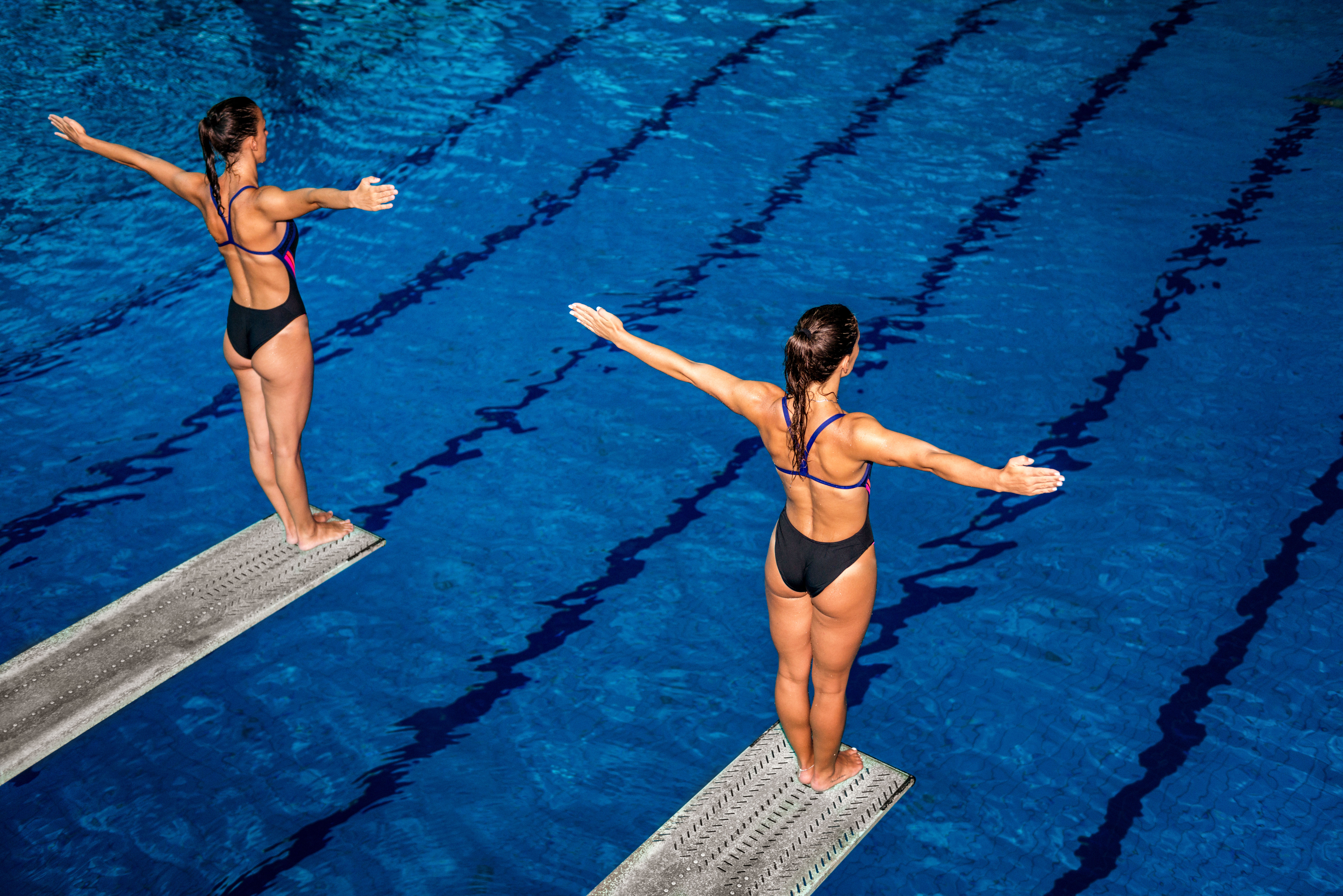 Two people diving in to a swimming pool